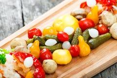 Blandade inlagda grönsaker - surkålkål, peppar, gurkor, tomater, lökar, champinjoner och örter på skärbräda Royaltyfria Foton