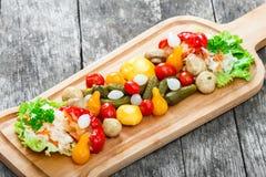 Blandade inlagda grönsaker - surkålkål, peppar, gurkor, tomater, lökar, champinjoner och örter på skärbräda Fotografering för Bildbyråer