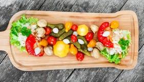Blandade inlagda grönsaker - surkålkål, peppar, gurkor, tomater, lökar, champinjoner och örter på skärbräda Royaltyfri Bild