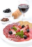 Blandade köttläckerheter på en platta, en peppar, oliv och ett vin Royaltyfria Foton