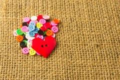 Blandade knappar och hjärtaknappar på ljus - brun säckbakgrund Royaltyfria Bilder