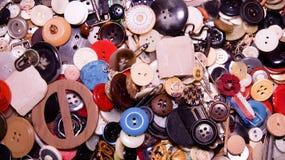 Blandade knappar Olikt i färg som mestadels är plast-, några som är trä Högen av knappar stänger sig upp bakgrund Arkivbilder