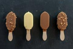 Blandade mini- glassar på pinnen på svart arkivbild