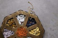 Blandade muttrar på en grå bakgrund i träask Sund mat och mellanmål Top beskådar royaltyfri bild