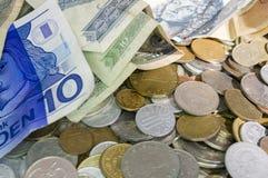Blandade mynt och pengar. Arkivbild