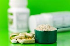 Blandade naturliga mattilläggpreventivpillerar och proteinpulver i plast- sked på grön bakgrund Fotografering för Bildbyråer