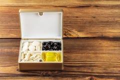 Blandade naturliga mattilläggpreventivpillerar i behållaren, omega 3, vitamin c, carotenekapslar på träbakgrund Royaltyfri Fotografi