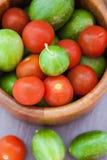 Blandade nya färgrika gurkor och körsbärsröda tomater Royaltyfria Bilder