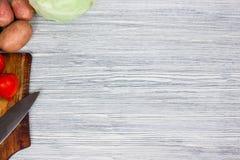 Blandade nya grönsaker med punkt för bästa sikt för bakgrund för kniv vit trä Arkivbilder