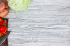 Blandade nya grönsaker med punkt för bästa sikt för bakgrund för kniv vit trä Royaltyfri Bild
