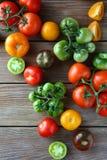 Blandade organiska tomater på bräden Royaltyfri Foto