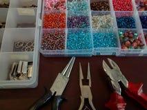 Blandade pärlor i olika format och färger i klart plast- fall royaltyfri foto