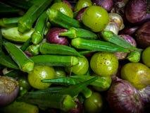 blandade rå grönsaker med sockerkaksbit i form av ett finger, lök, amla royaltyfria bilder