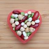 Blandade skidfruktbönor i en hjärtabunke arkivfoton