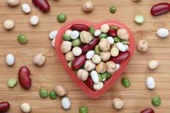 Blandade skidfruktbönor i en hjärtabunke royaltyfria bilder