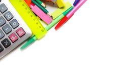 Blandade skolatillförsel, inklusive pennor, blyertspennor, sax, lim och en linjal, på en vit bakgrund arkivbild