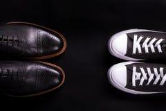Blandade skor Oxford och gymnastikskosko på svart bakgrund Olik stil av manmode Jämför formellt tillfälligt Top beskådar snut Royaltyfria Bilder