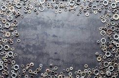 Blandade skruvmuttrar - och - bultram på metallbakgrund arkivfoto
