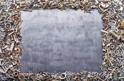 Blandade skruvmuttrar - och - bultram på metallbakgrund arkivfoton