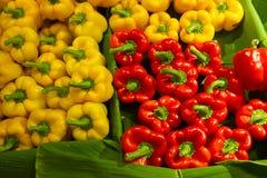 Blandade spanska peppar i olika färger på bananen spricker ut på fr Arkivbilder