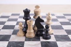 Blandade svartvita trächesspieces på schackbrädet Arkivfoton