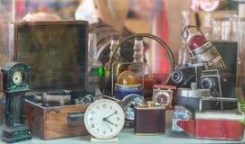 Blandade tappningobjekt, klockor, kameror, flaskor, sextanten, lampor bakom shoppar fönstret arkivfoton