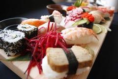 Blandade typer av sushi på bambutabellen med hashipinnar och shoyu royaltyfri fotografi