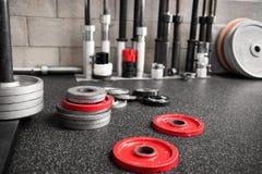 Blandade vikter spridde på golvet av en idrottshall Royaltyfri Fotografi