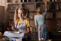Blandande ägg för förtjust liten flicka som sitter på tabellen Royaltyfria Foton