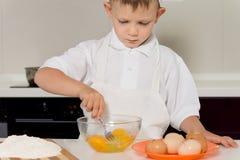 Blandande ägg för liten pojke i en bunke Fotografering för Bildbyråer