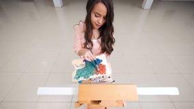 Blandande blått och apelsin för flicka som gör den högra färgen lager videofilmer