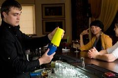 Blandande coctailar för bartender för lyckliga kunder arkivfoto
