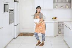 Blandande deg för ung hemmafru i köket royaltyfria foton