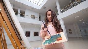 Blandande färger för kvinna som målar en bild i konstgalleri arkivfilmer