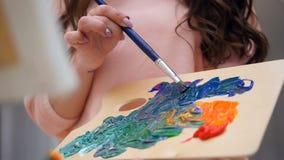 Blandande färger för kvinnlig konstnär för henne bild arkivfilmer