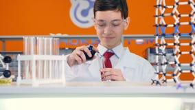 Blandande flytande för högstadiumpojke i provrör i vetenskapsgrupp stock video