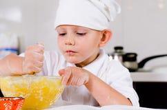 Blandande ingredienser för liten pojke för en kaka i en bunke royaltyfria foton