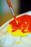 Blandande målarfärger på paletten Royaltyfri Foto