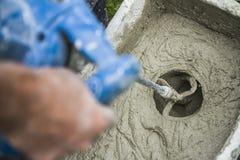 Blandande murbruk för arbetare med en drillborr Arkivbilder