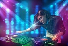 Blandande musik för Dj-flicka i en klubba med blåa och purpurfärgade ljus Royaltyfria Foton