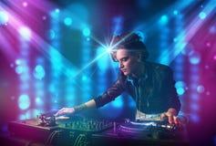 Blandande musik för Dj-flicka i en klubba med blåa och purpurfärgade ljus Royaltyfri Fotografi