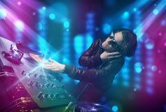 Blandande musik för Dj i en klubba med blåa och purpurfärgade ljus Arkivfoton