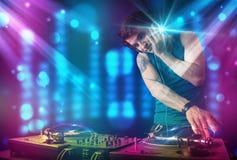 Blandande musik för Dj i en klubba med blåa och purpurfärgade ljus Royaltyfria Bilder
