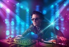 Blandande musik för Dj i en klubba med blåa och purpurfärgade ljus Royaltyfri Foto