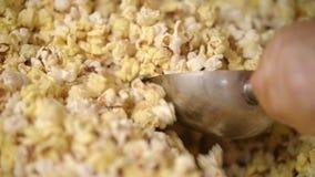 Blandande popcorn för arbetare i popcornmaskin med skopan Förbereda mat för film lager videofilmer