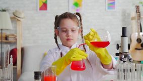 Blandar den ton?riga bloggeren f?r flickan i ett vitt lag och exponeringsglas i laboratoriumet, agens lager videofilmer