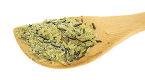 Blandar lösa ris för långt korn på en wood sked Arkivfoton