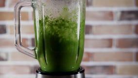 Blandare med den gröna smoothien på köket lager videofilmer