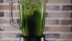 Blandare med den gröna vegetariska coctailen på köket arkivfilmer