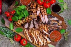 Blandat grillat köttuppläggningsfat Blandat läckert grillat kött med grönsaken Fotografering för Bildbyråer